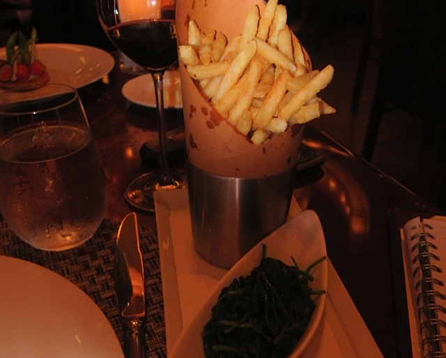 Individual cone of french fries, with garlicky spinach on the side