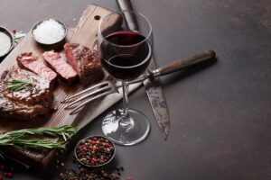 Grilled ribeye beef steak with red wine, herbs and spices on sto